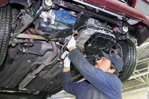 Мужчина ремонтирует подвеску авто