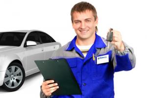 Автомеханик держит в руке ключи от машины