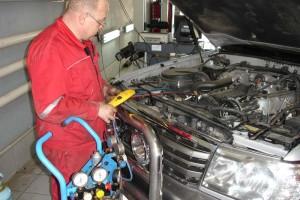 Мужчина ремонтирует авто на СТО
