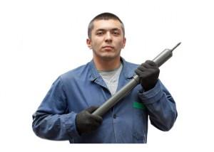 Автомобильный амортизатор у мужчины в руках
