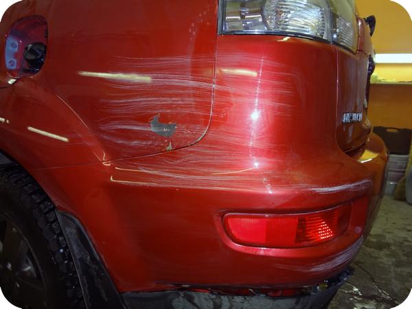 Поцарапанный бампер на красном авто