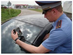 Инспектор ГАИ замеряет светопропускаемость лобового стекла