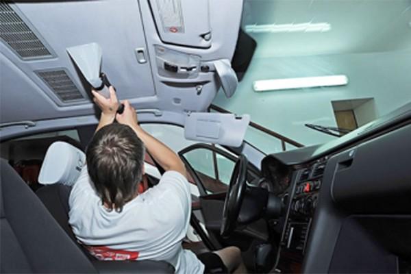 Мужчина чистит потолок автомобиля